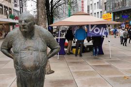 """Ein Pavillon steht in der Fußgängerzone, im Vordergrund steht die Statue """"der Dicke""""."""
