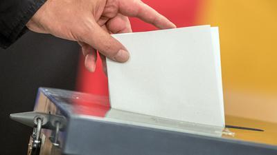 Ein Wähler wirft seinen Stimmzettel zur Bundestagswahl in die Wahlurne.