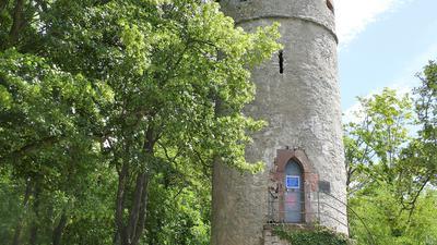 Ein steinerner Turm mit Treppenaufgang im Grünen.