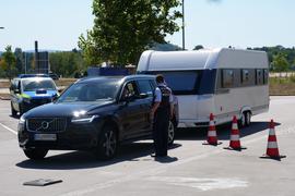 Ein Polizist steht vor einem schwarzen Auto, das ein weißes Wohnmobil zieht. Im Hintergrund steht ein Polizeiauto.