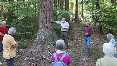 Zwei Männer stehen vor einer Gruppe Menschen, einer der Männer hat die rechte Hand am Baum, in der linken Hält er ein Stück Rinde.