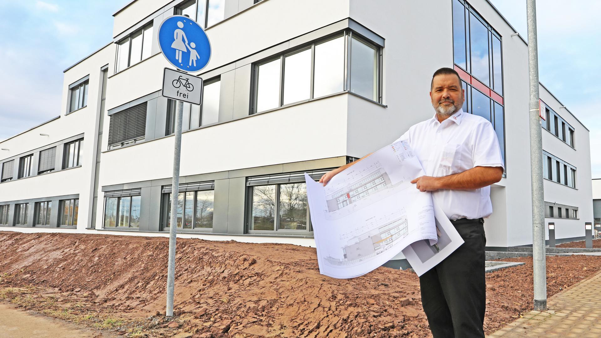 """Geschäftsführer Steffen Stüber vor dem neuen Firmengebäude der Firma Pfirmann im Buchbusch in Pforzheim mit den Plänen für ein """"Niedriginfektionsgebäude"""" in Weingarten."""