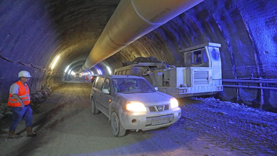 Ein Auto fährt in der staubigen Hauptröhre des künftigen Arlingertunnels. Oben im Bild das Rohr für die Frischluftzufuhr.