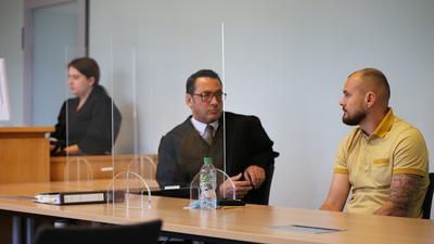 Eine Frau sitzt links im Bild, rechts zwei Männer hinter Glasscheiben.