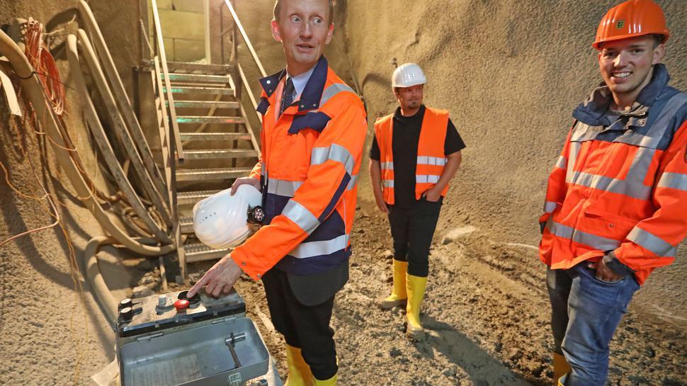 Baureferatsleiter Jürgen Genthner, Sachgebietsleiter Michael Schwab und Projektleiter Ralf Weisenburger (von links) vom Regierungspräsidium Karlsruhe beim Termin auf der Baustelle für den künftigen Arlingertunnel. Genthner zeigt den Sprengknopf.