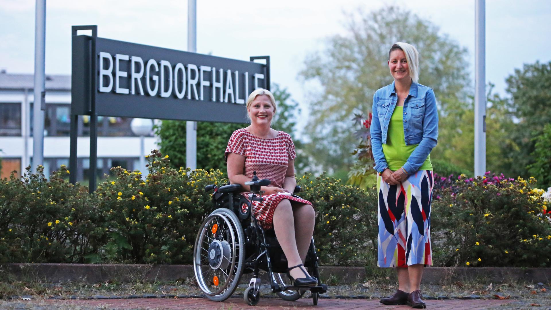 Zwei Frauen, eine davon im Rollstuhl.
