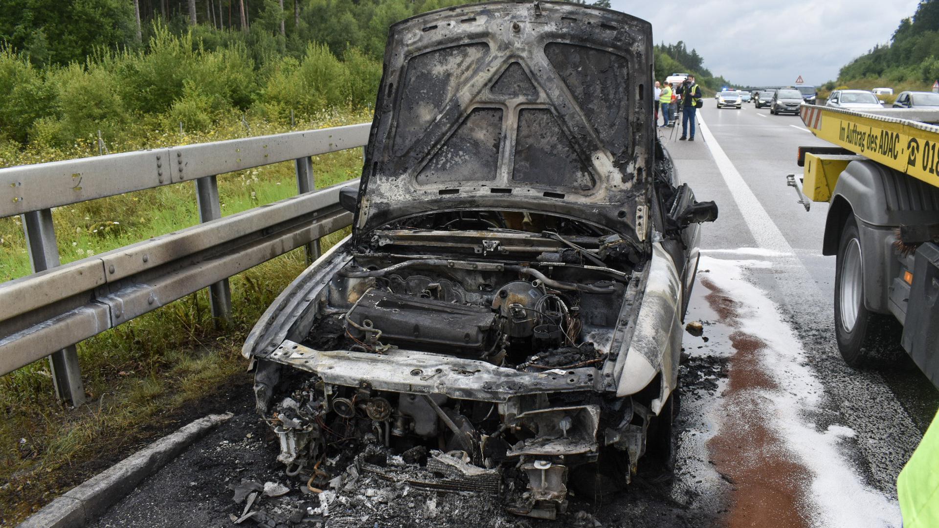 Ausgebranntes Auto auf dem Seitenstreifen der Autobahn.