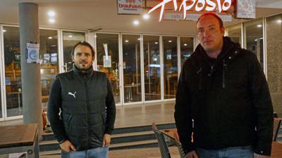 Zwei Männer (Bruno Martins, Tobias Feucht) stehen vor dem erleuchteten Aposto mit traurigem Gesichtsausdruck.