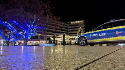 Die Weihnachtsbeleuchtung am Rathaus in Pforzheim können in der Nacht zum Sonntag immerhin die Polizisten genießen, die die Einhaltung der Ausgangssperre überwachen. Ein Polizeiauto steht vor dem gold und blau illuminierten Rathaus-
