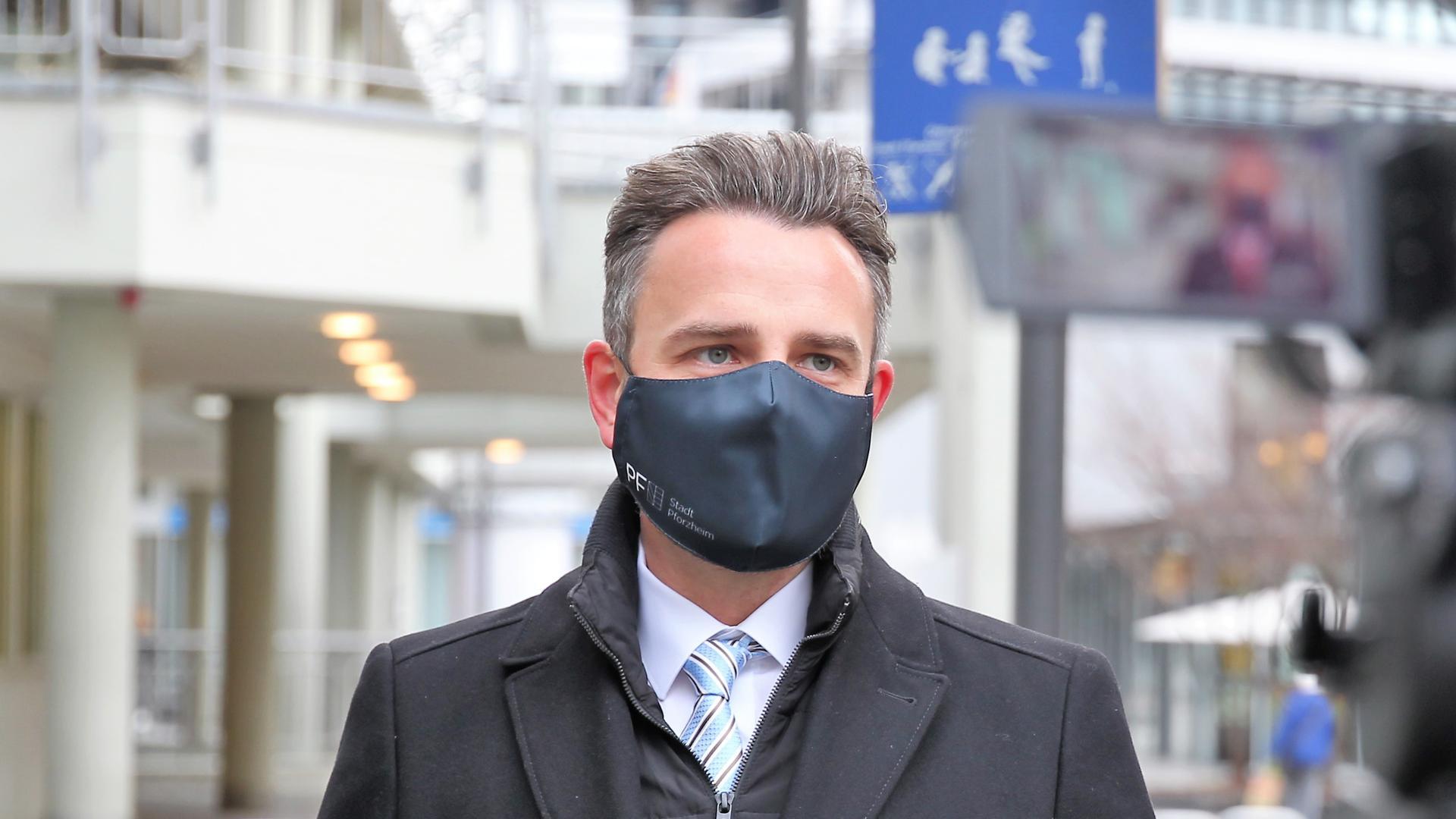 Pforzheims Oberbürgermeister Peter Boch (CDU) steht in der Innenstadt vor einer TV-Kamera. Er macht das Sozialministerium von Manne Lucha (Grüne) für die schleppende Umsetzung einer Corona-Hotspot-Strategie verantwortlich.