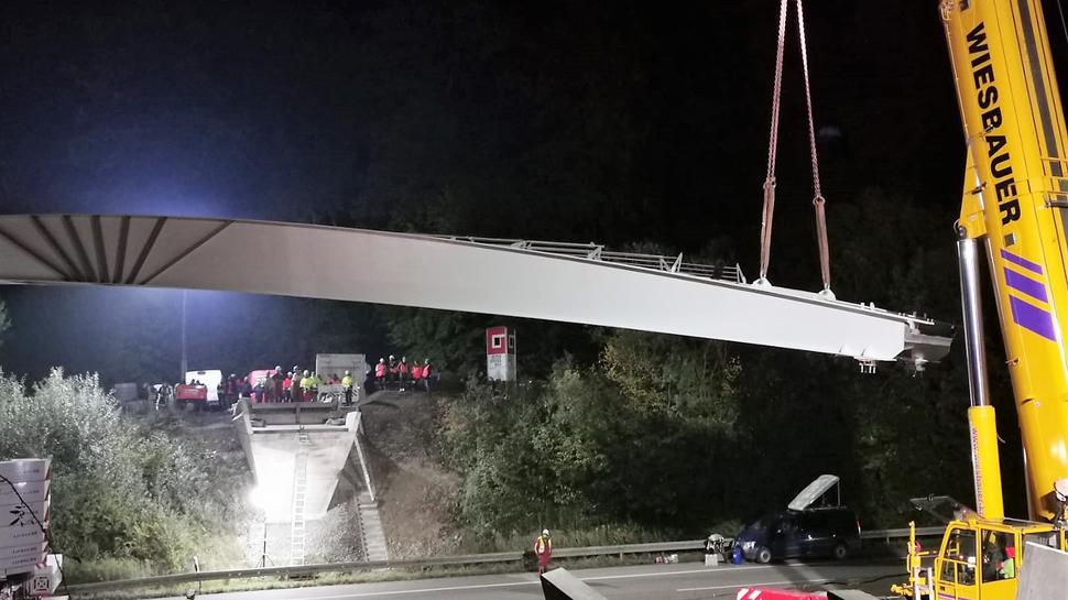 Ein Spezialkran bringt den Koloss aus Stahl und Beton am Sonntag gegen 2 Uhr in Position. Bauarbeiter stehen auf beiden Seiten der Brücke und schauen gespannt zu.