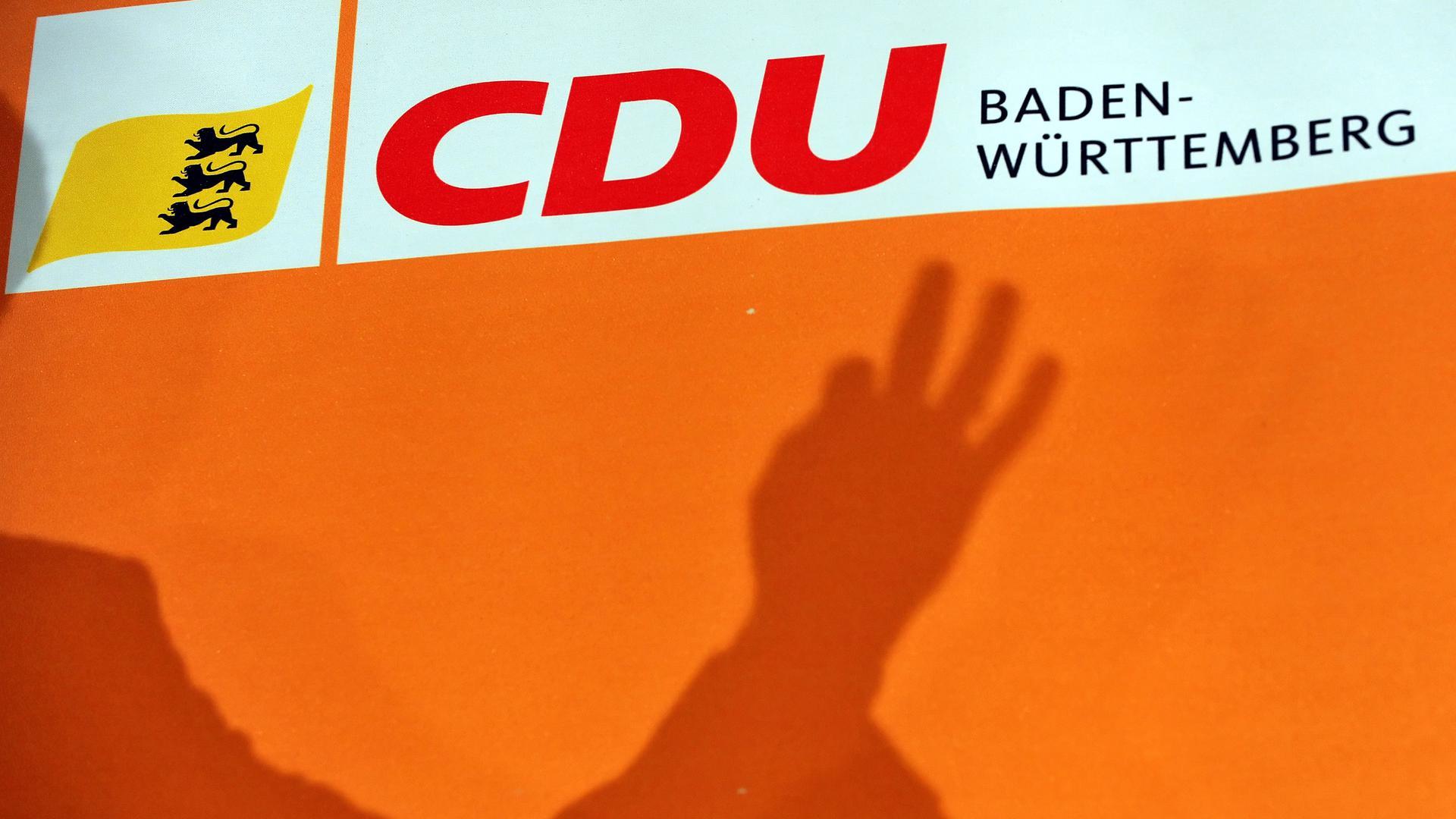 Der Schatten einer Hand über dem Parteilogo der CDU Baden-Württemberg