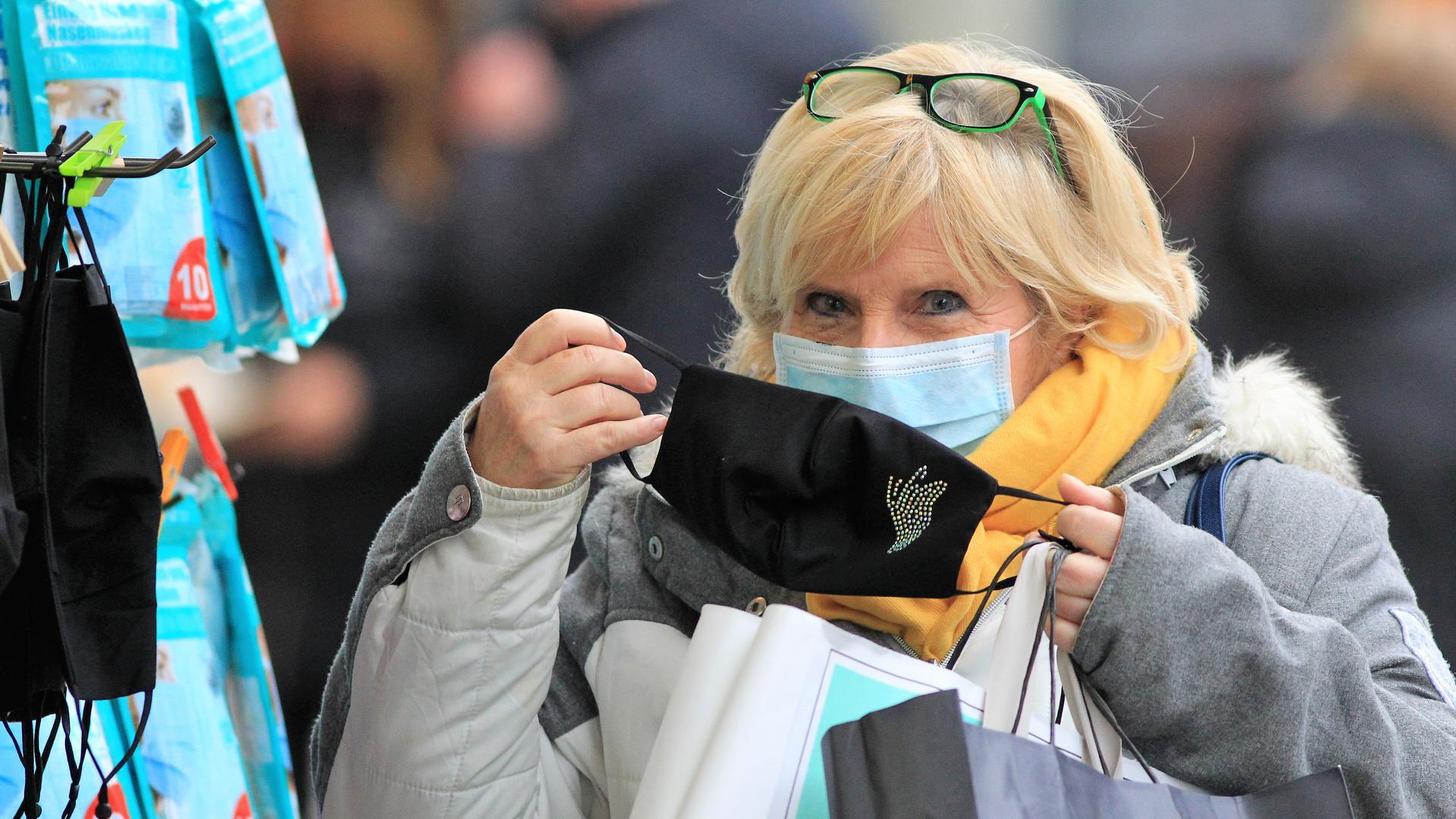 Eine Passantin steht vor einem Bekleidungsgeschäft in der Pforzheimer Fußgängerzone und probiert eine modische Maske an.