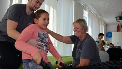 Mit Spaß und Eifer dabei: Die neunjährige Clara trainiert mit Helfer Bakir und Daniela Dorschner-Geerlofs an Seilen, um die Rumpfstabilität zu verbessern. Viele Wochen hat das Mädchen schon in der Pforzheimer Privatklinik verbracht mit dem großen Ziel, eines Tages wieder laufen zu lernen.