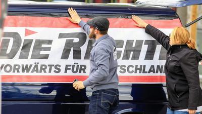 """Mit der Rechten: Aktivisten der Partei """"Die Rechte"""" bekleben vor einer Demonstration in Pforzheim ein Banner auf einen Kleinbus."""