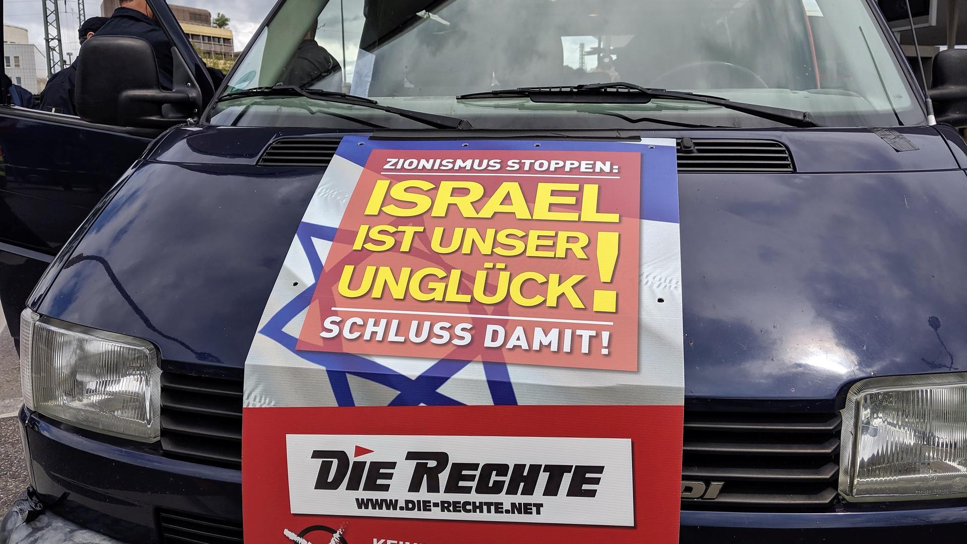 """Plakat auf einem Kleinbus am Pforzheimer Bahnhof: Isreal ist unsere Unglück, steht darauf. Grauzone der Meinungsfreiheit: Mit mehrdeutigen Wahlplakaten, hier bei einer Kundgebung in Pforzheim, provozierte die Kleinpartei """"Die Rechte"""" im Europawahlkampf 2019."""