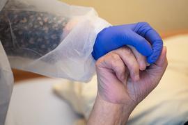 Eine Altenpflegerin in Schutzausrüstung hält die Hand eines Bewohners.