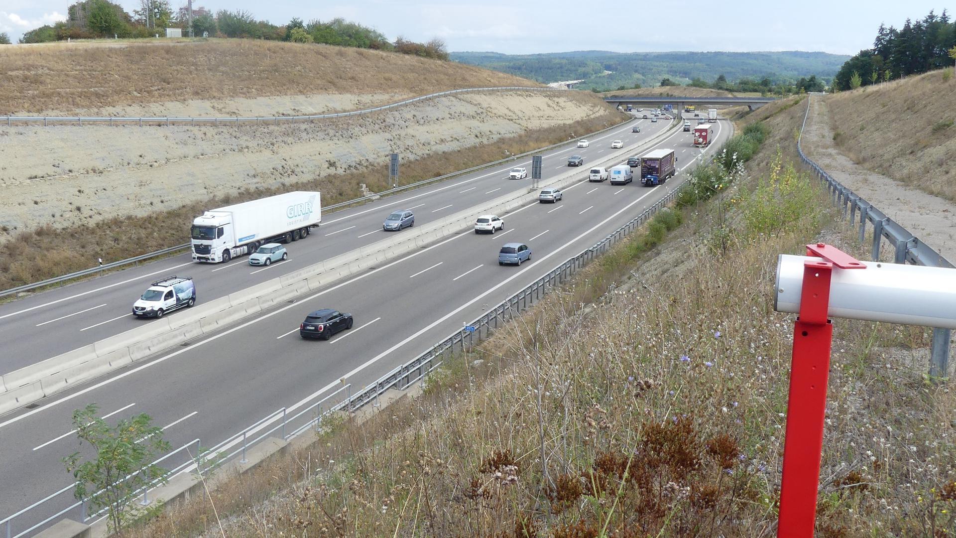 Eine Autobahn, auf der einige Autos fahren, links und rechts neben der Fahrbahn ist Grün.
