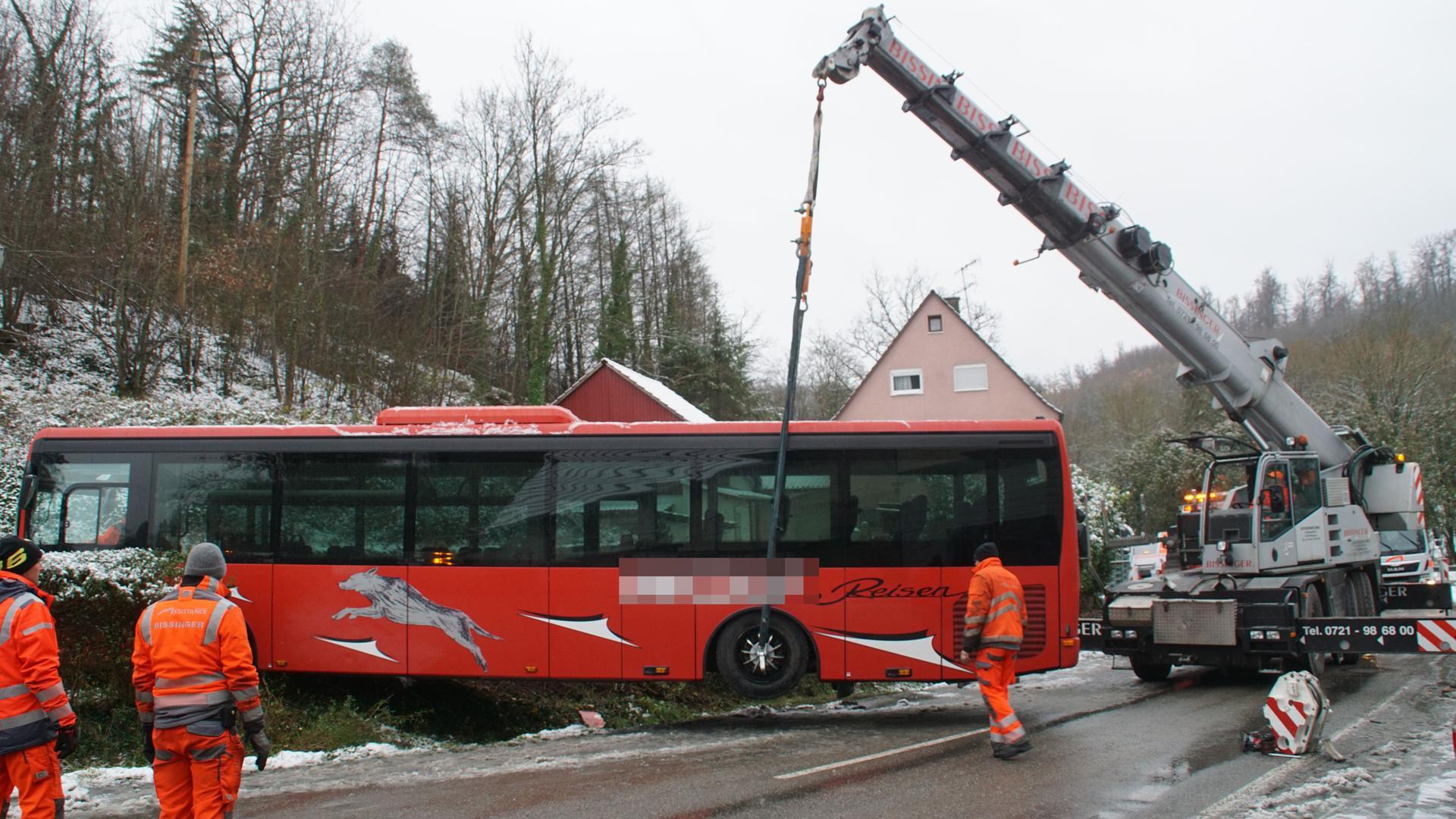 Ab durch die Hecke: Ein Bus kam am frühen Dienstag im Enzkeis von der Straße ab und steckte dann im Graben fest. Ein Kran hebt ihn gerade zurück auf die Straße.
