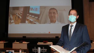 Landrat Bastian Rosenau hält den Haushalt 2021 in der Hand.