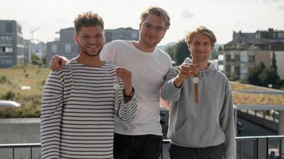 Einmal mit Mesh, einmal mit Kork: Sebastian Well, Johannes und Martin Boger (von links) präsentieren die Schwarzwald-Uhren.