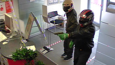 Zwei Männer stehen in einem Vorraum einer kleinen Bankfiliale, beide haben Helme auf, einer hält eine Pistole in der ausgestreckten Hand.