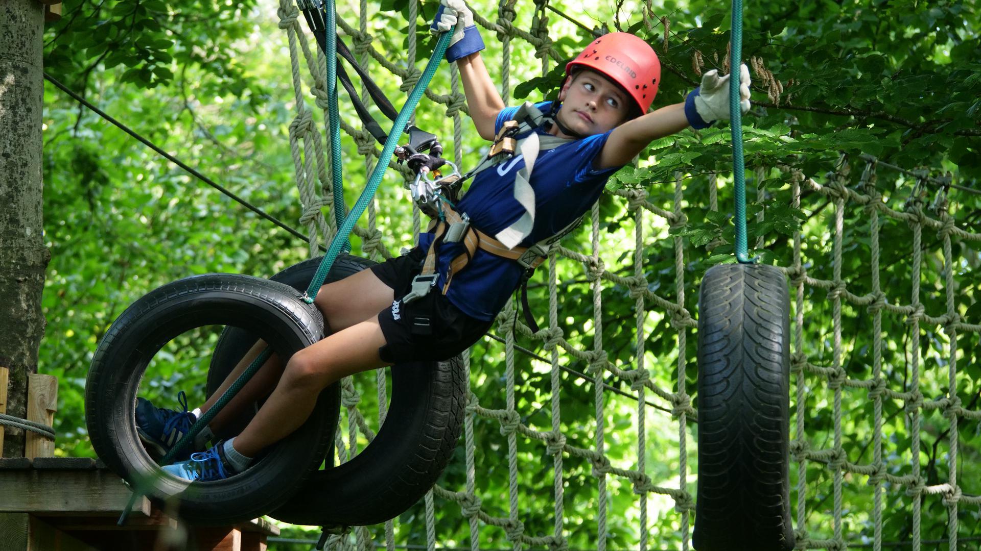 Gut geschützt hangelt sich der jugendliche Besucher in luftiger Höhe von Seil zu Seil