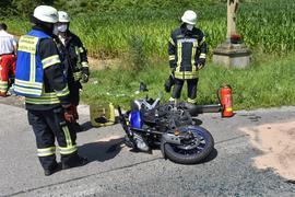 Einsatzkräfte der Feuerwehr Kämpfelbach stehen nach einem Unfall neben einem Motorrad, das auf der Straße liegt.