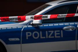 Ein Polizeiauto steht hinter einem Absperrband der Polizei.