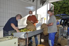Männer mit Äpfeln an Maschine