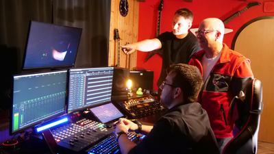 Begutachten gemeinsam das fertige Werk im Studio in Knittlingen: Patrick Zalas und Peter Schäfer vom DRK (stehend), sowie Johannes Riedl (sitzend)