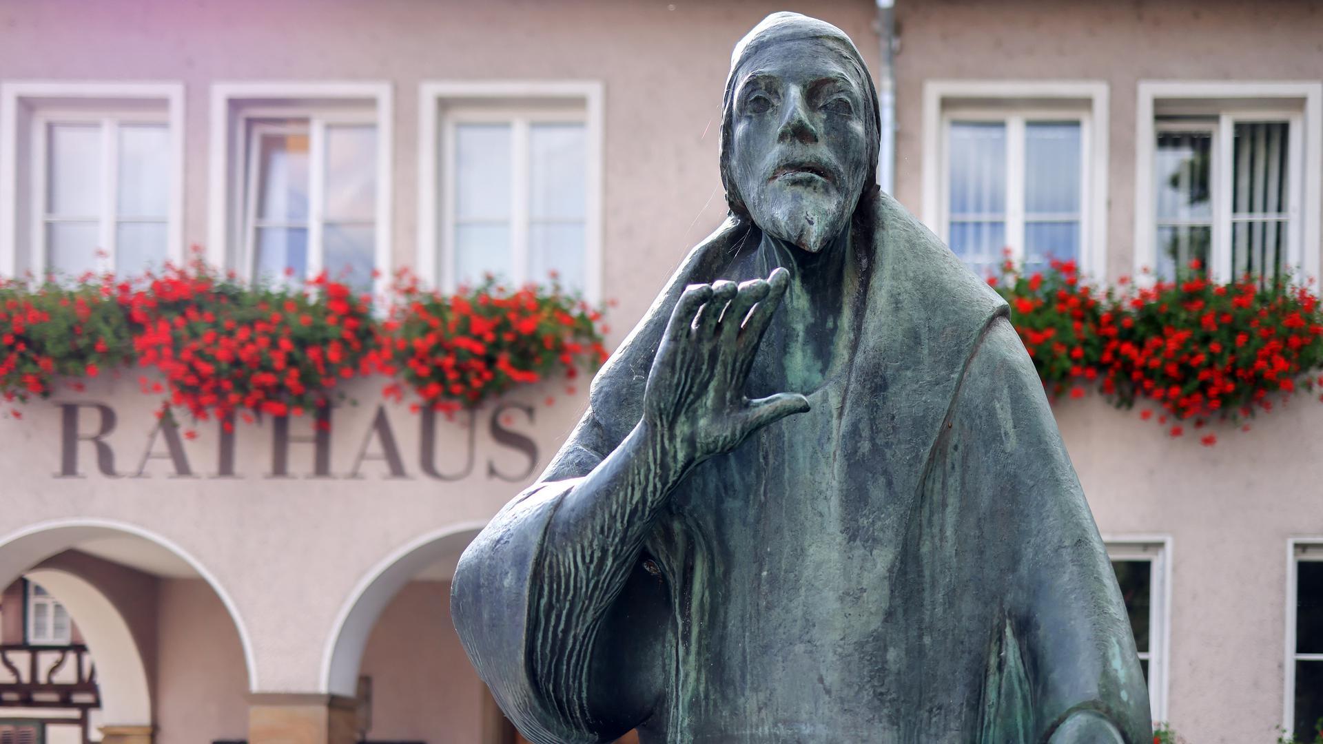 Die Faust-Figur vor dem Knittlinger Rathaus mit erhobener Hand.