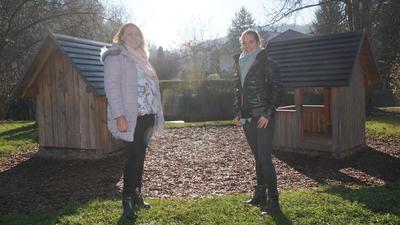 Zwei Frauen stehen vor zwei kleinen Häusern.