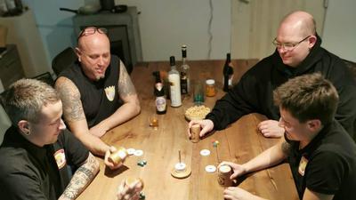 Vier Menschen sitzen am Tisch und spielen ein Würfelspiel.
