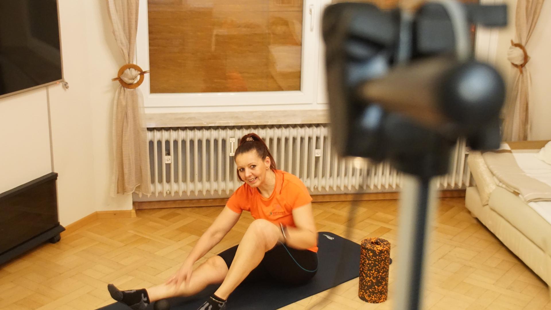 Frau zeigt Fitnessübungen vor Kamera.
