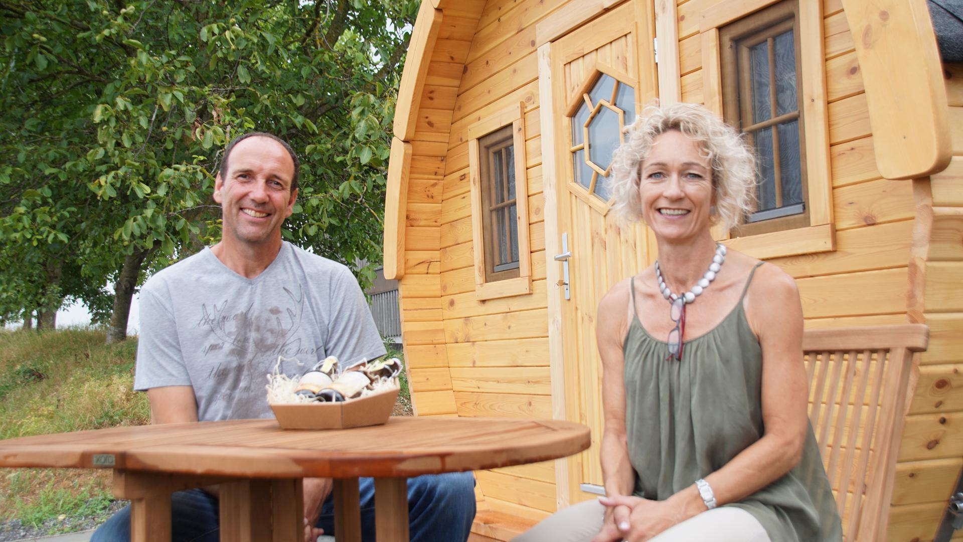 Sabine Büttner und Martin Ehrismann sitzen vor einem Holzfass im Grünen.