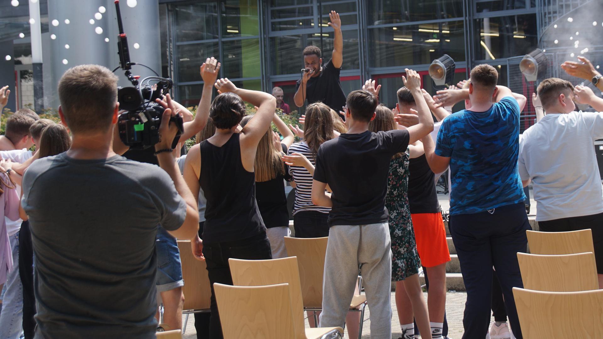 Rapper Cossu tritt vor dem Königsbacher Bildungszentrum auf.