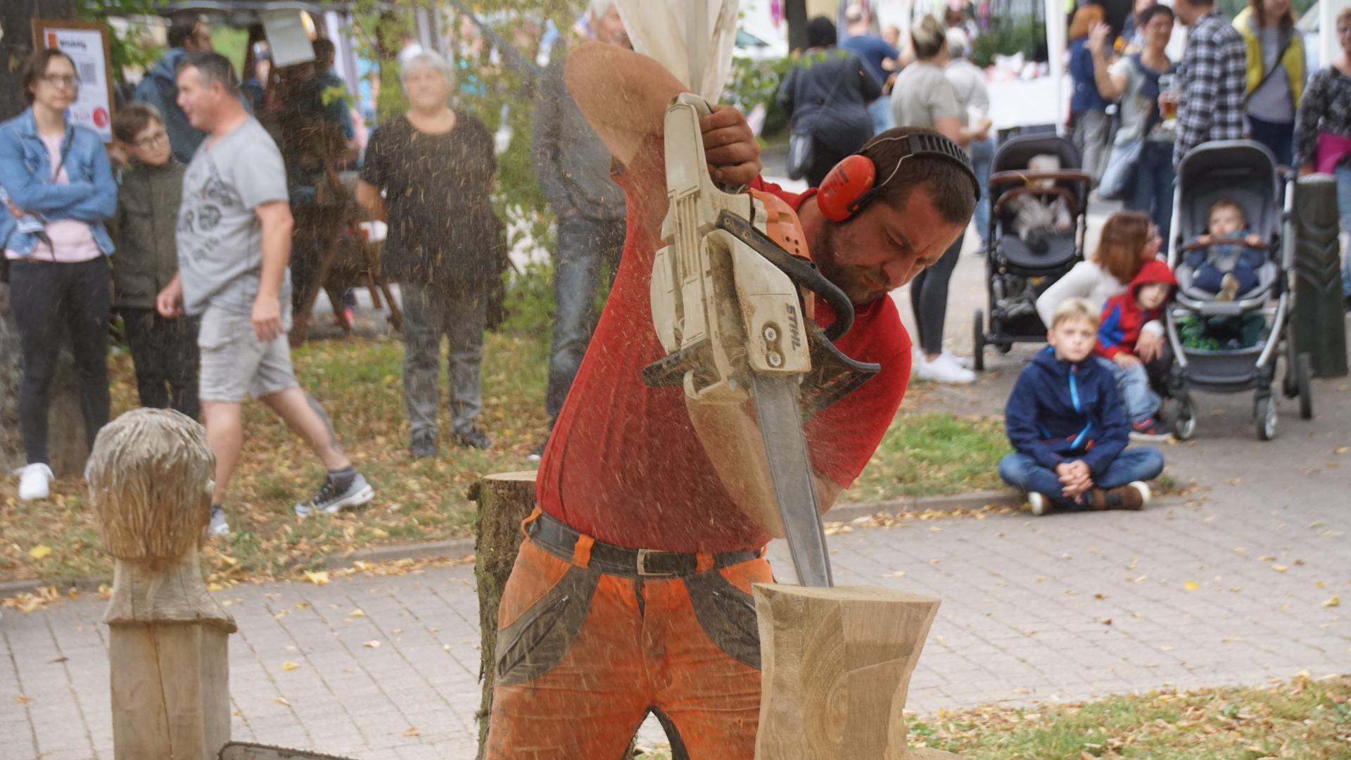 Ein Künstler mit der Kettensäge: Andreas Drost sägt Skulpturen aus Eichenstämmen und viele schauen ihm dabei zu.