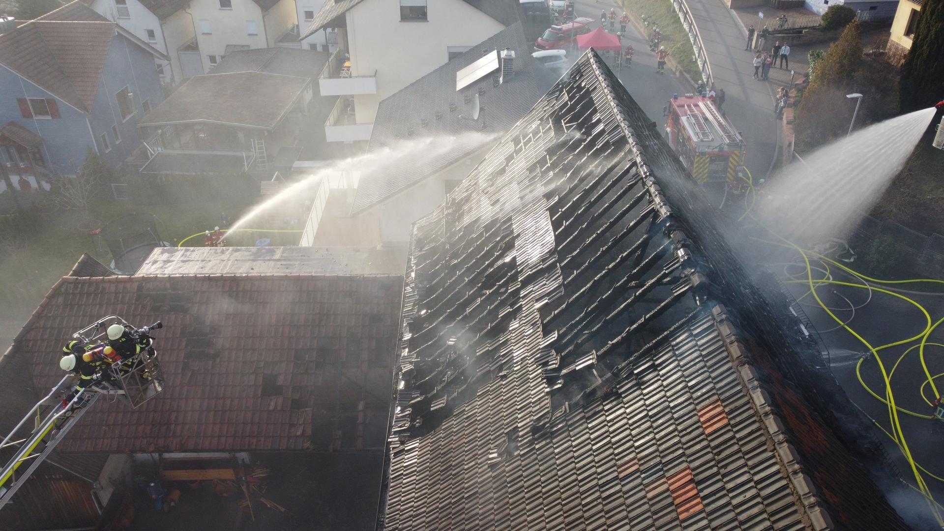 Blick von oben in eine brennende Scheune. Die Feuerwehr löscht.