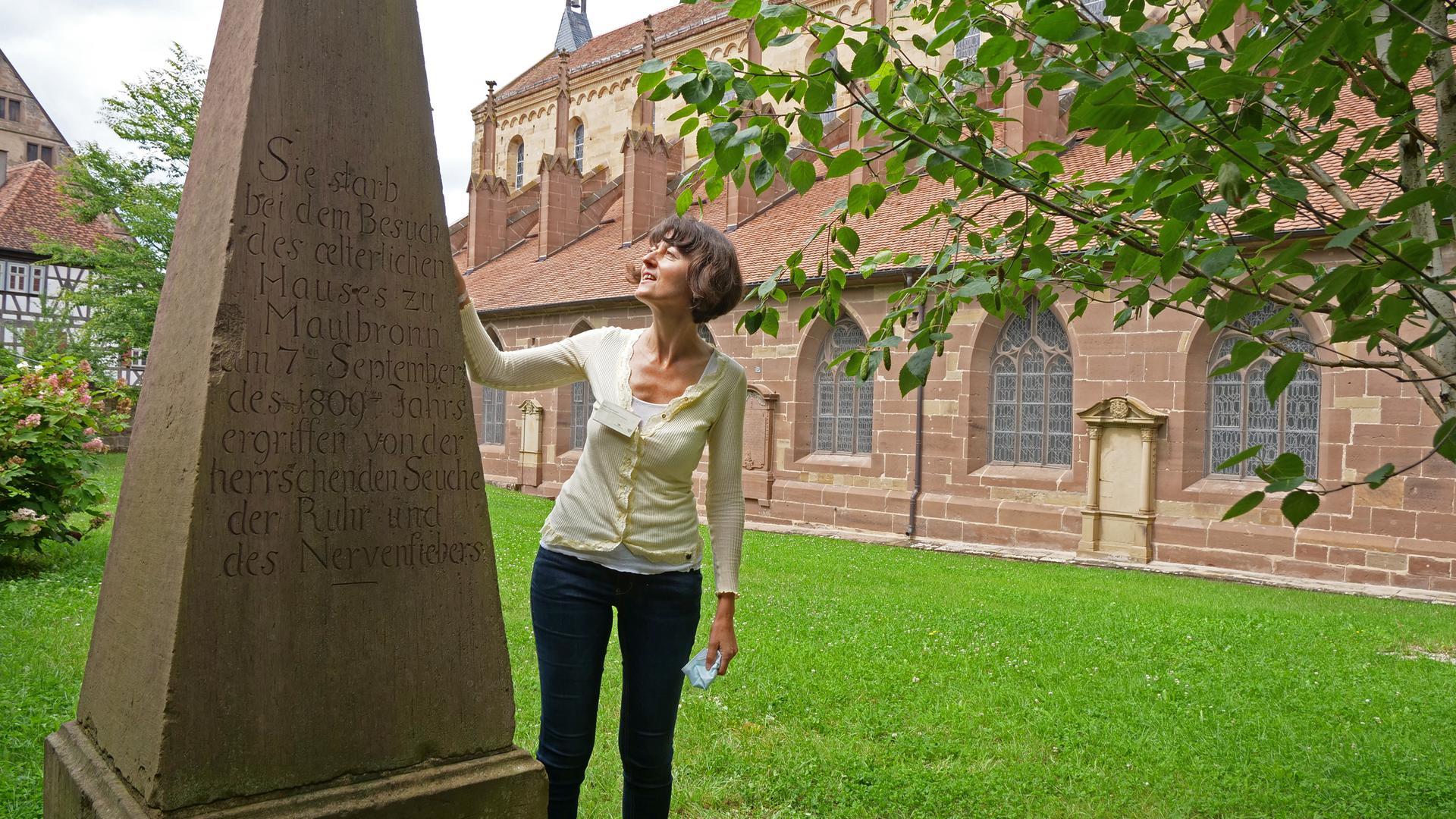 Eine Frau steht neben einem Obelisken