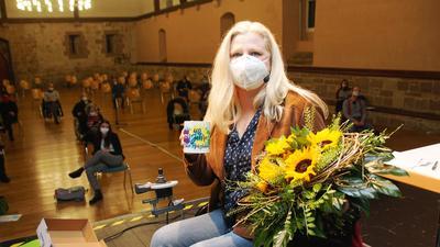 Eine Frau im Rollstuhl hält eine Tasse und einen Blumenstrauß in der Hand.