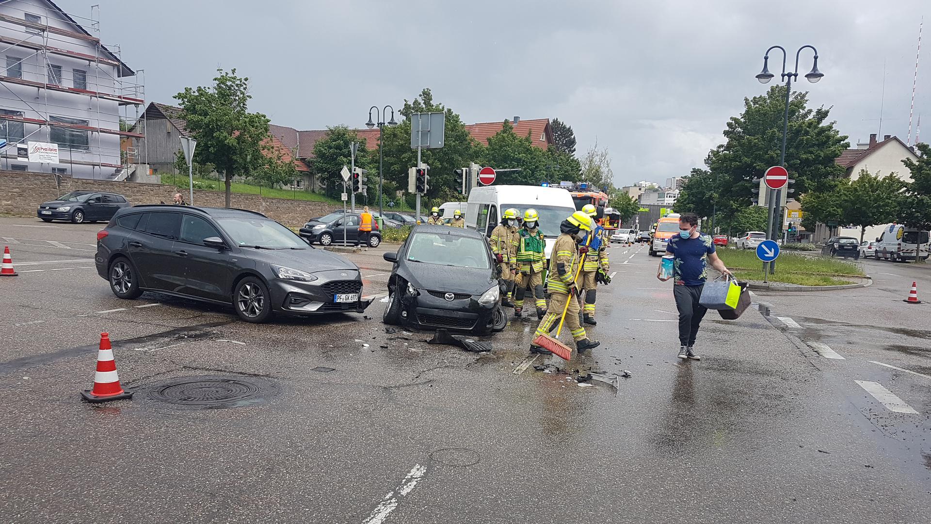 Zwei demolierte Autos und Feuerwehr auf einer Kreuzung