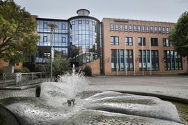 Das Rathaus in Mühlacker mit seiner Glas- und Steinfassade. Im Vordergrund plätschert ein Brunnen.