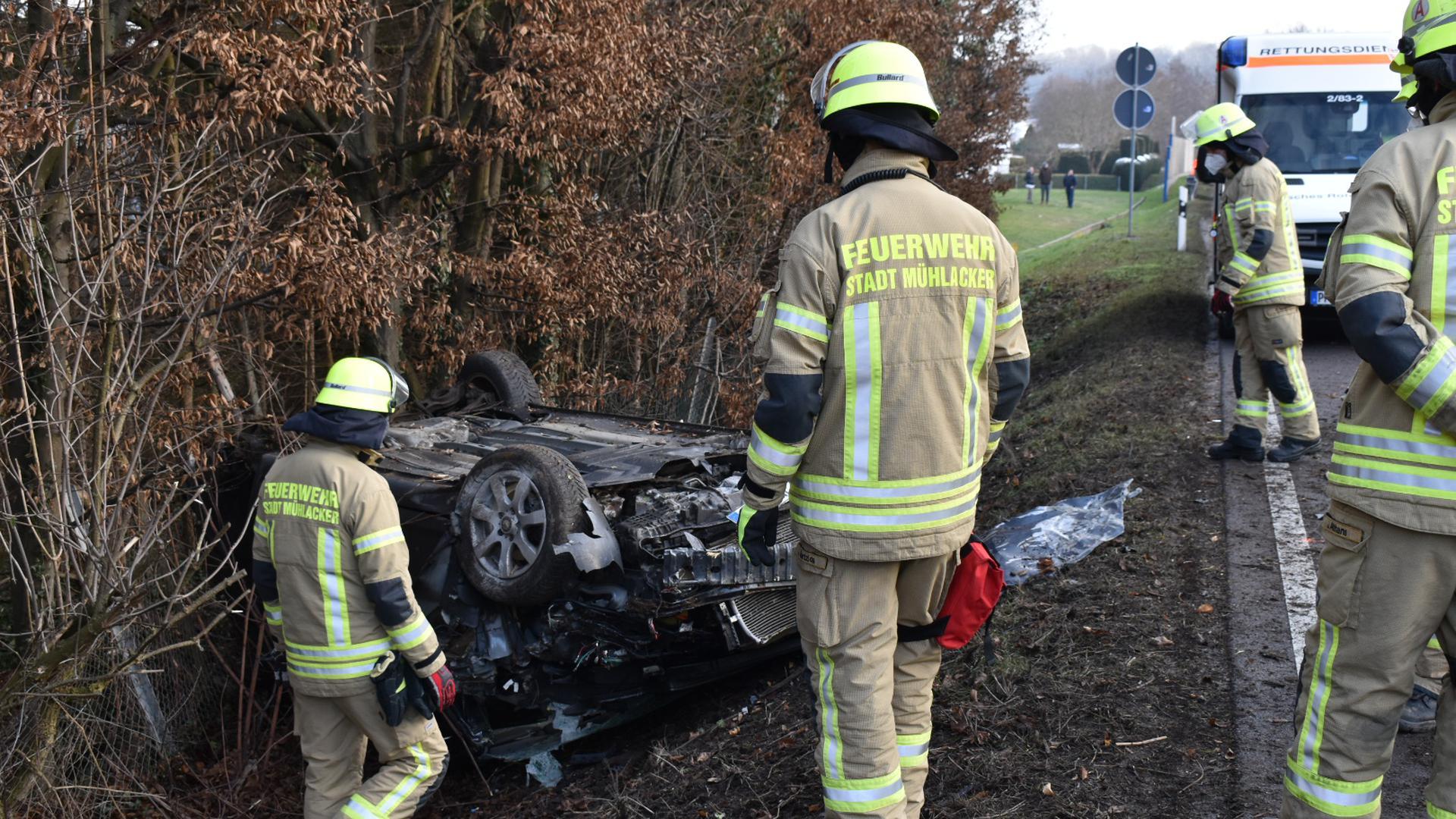 Einsatzkräfte der Feuerwehr untersuchen ein stark beschädigtes Autos neben der B10.