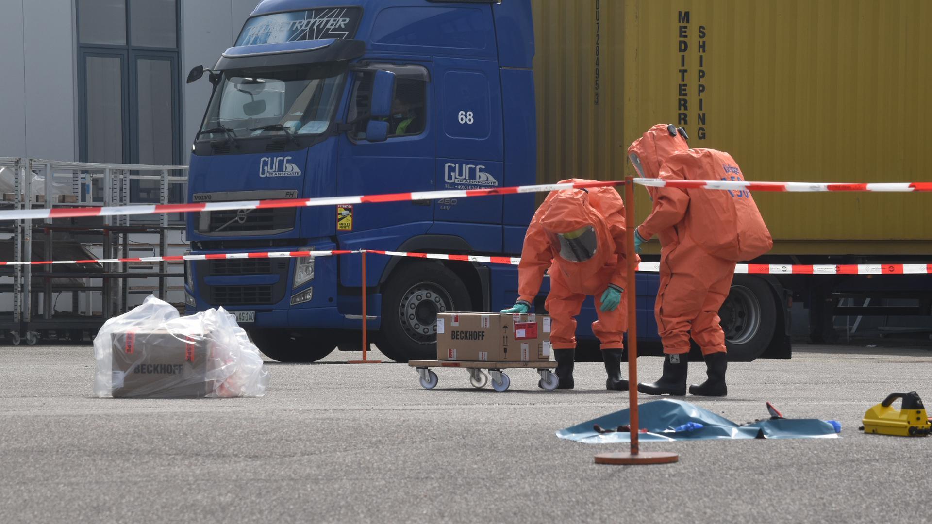 Feuerwehrleute in Schutzanzügen untersuchen das verdächtige Paket.