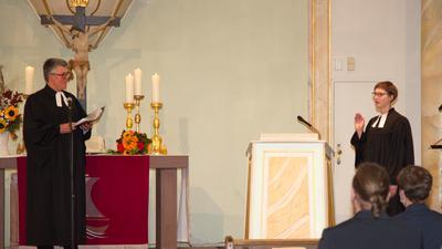 Investiturgottesdienst in der Stadtkirche Neuenbürg: Dekan Joachim Botzenhardt und die neue Arnbacher Pfarrerin Charlotte Moskaliuk stehen in Talare gekleidet vor einem Altar.