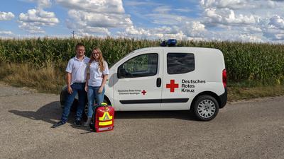 Tobias Wichmann und Luisa Wüst vom DRK-Ortsverein Neulingen stehen vor einem Auto des DRK-Ortsvereins Neulingen.