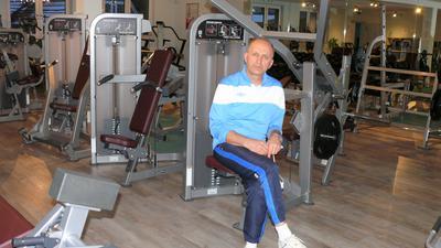 Mann sitzt auf Trainingsvorrichtung