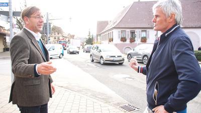 Zwei Männer stehen an einer Kreuzung, im Hintergrund Autos.