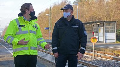 Zwei Männer stehen am Bahnhof